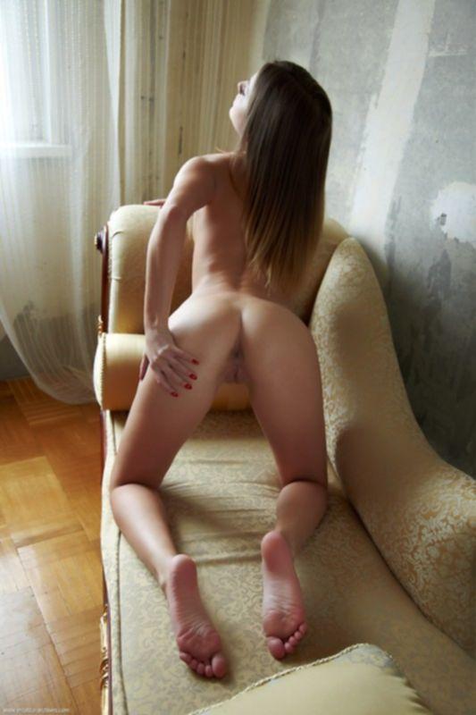 Голая модель с красивыми ногами позирует на диване