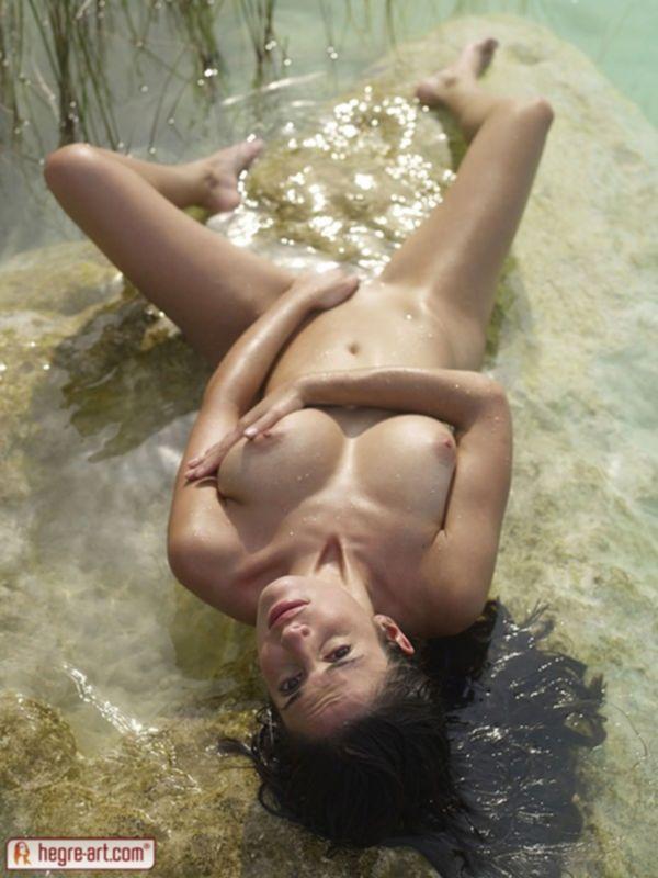 Красотка с большой грудью возле воды на камне