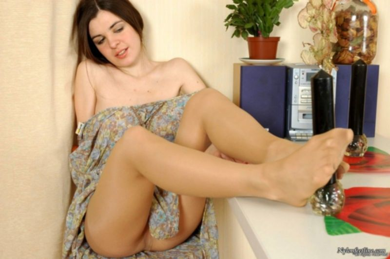 Девушка с большими сиськами показывает ступни ног в колготках