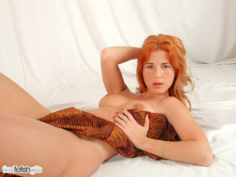 Рыжая девушка в спандексе садится на шпагат
