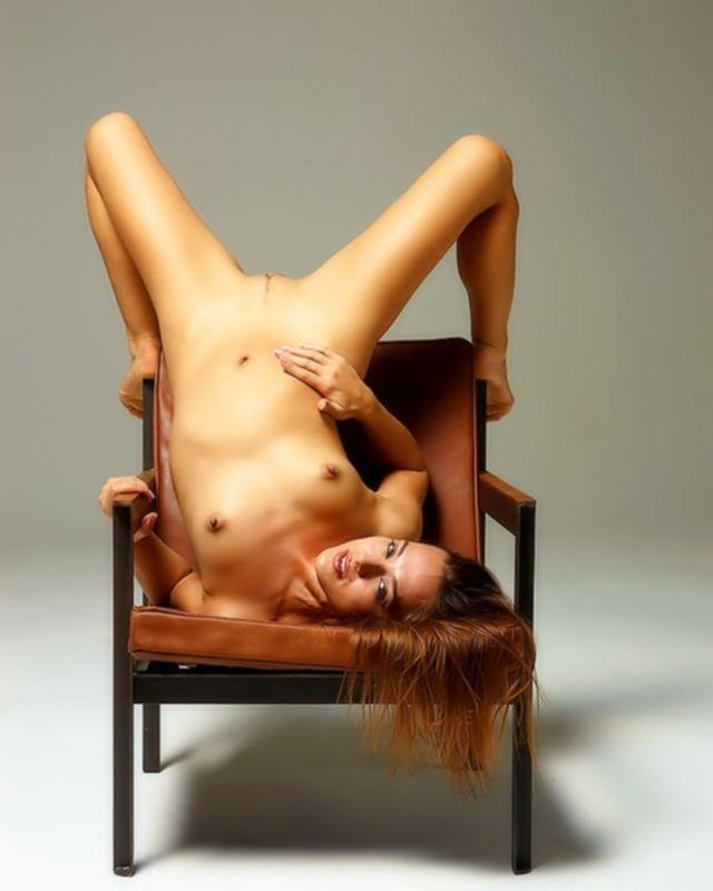 Голая девушка шатенка сидя на стуле показывает растянутые половые губки