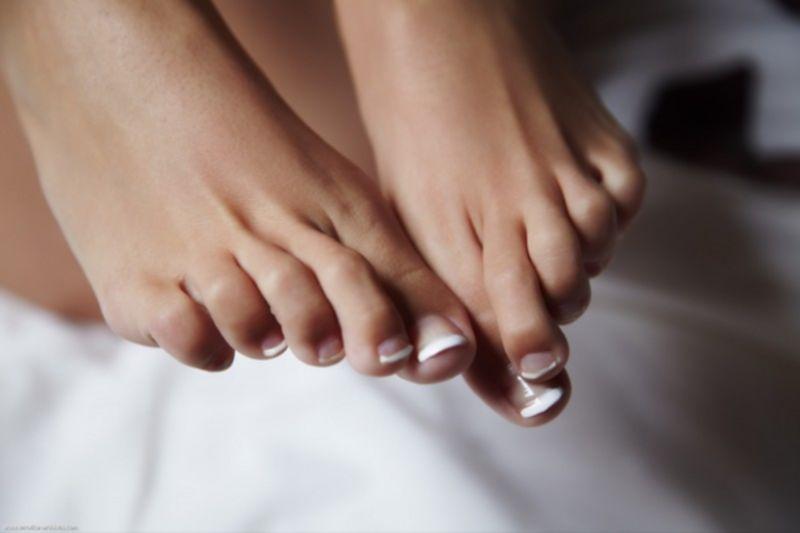 Красивая брюнетка показывает педикюр на пальчиках ног